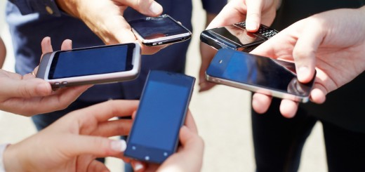 Close up of friends with circle of smart phones.